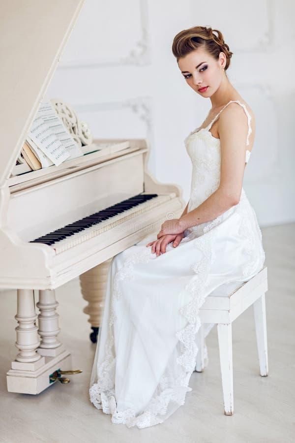 Красивая женщина около белого рояля стоковые изображения