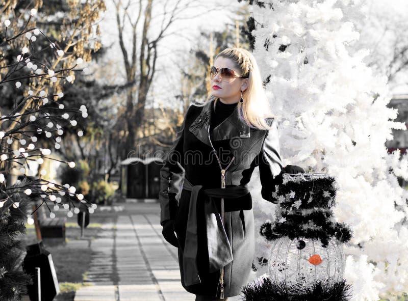 Красивая женщина около ели и снеговика, черно-и стоковое фото rf