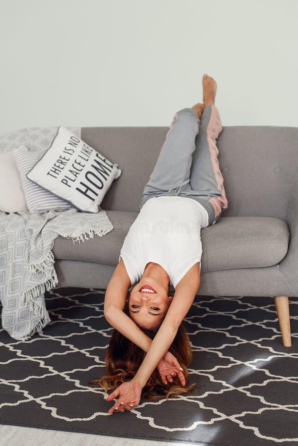 Красивая женщина ослабляя на сером кресле с головой вверх ногами Милая девушка имея потеху на уютном доме в ленивом дне стоковые изображения rf