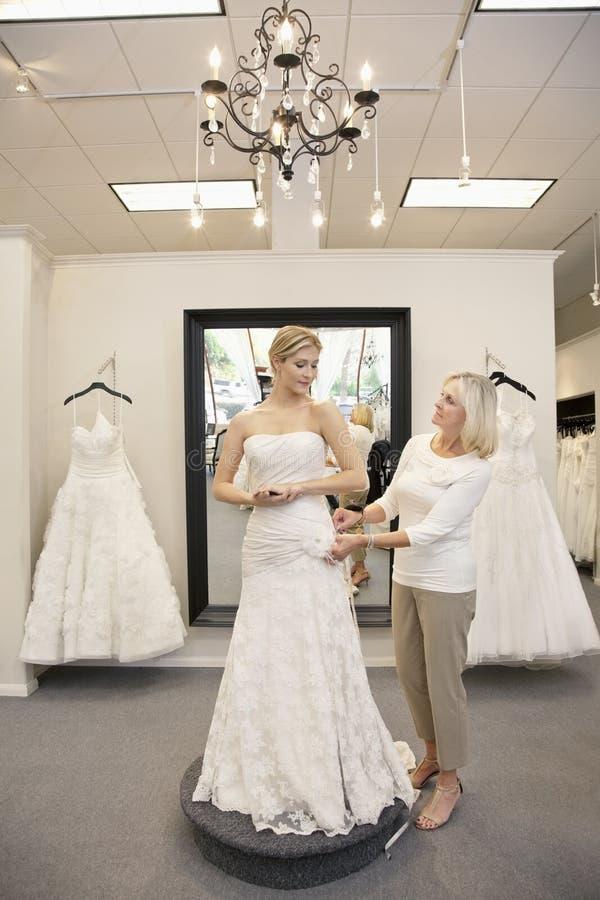 Красивая женщина одевала как невеста с старшей порцией работника в bridal магазине стоковое изображение