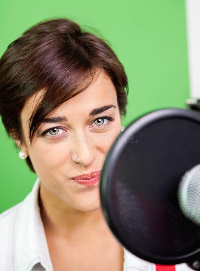 Красивая женщина поя в студии звукозаписи стоковая фотография rf