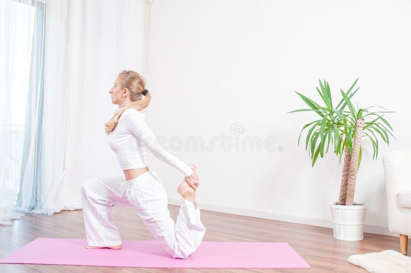 Красивая женщина практикует йогу дома на циновке йоги стоковое фото rf