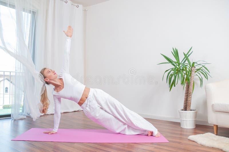 Красивая женщина практикует йогу дома на циновке йоги, девушке делая представление Camatkarasana стоковое фото rf