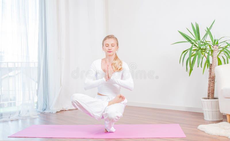 Красивая женщина практикует йогу дома на циновке йоги, девушке делая половинное представление баланса пальца ноги лотоса стоковое изображение