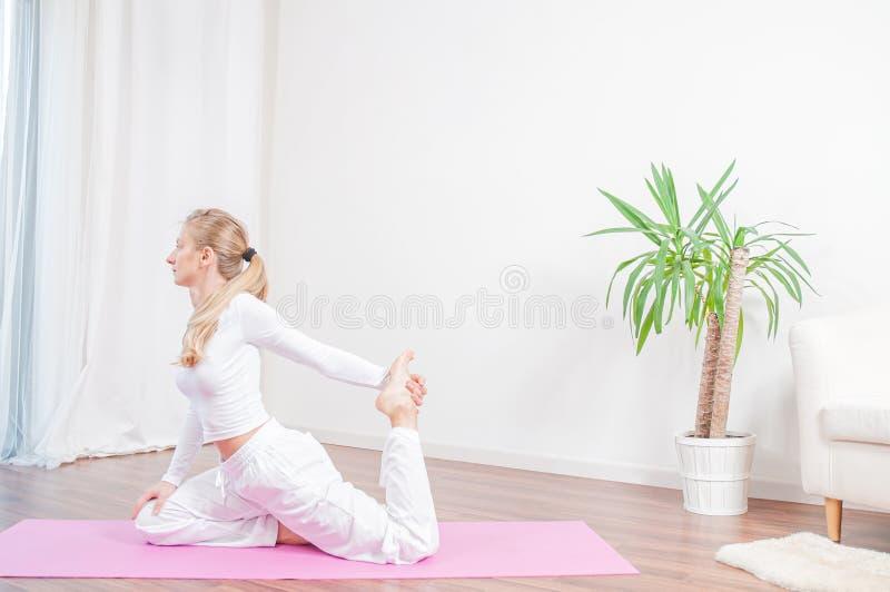 Красивая женщина практикует йогу дома на циновке йоги, девушке делая представление Eka Pada Rajakapotasana стоковые изображения