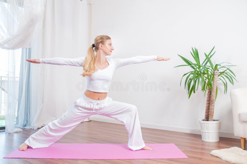 Красивая женщина практикует йогу дома на циновке йоги, девушке делая тренировку Virabhadrasana, стоя в представлении воина стоковое изображение