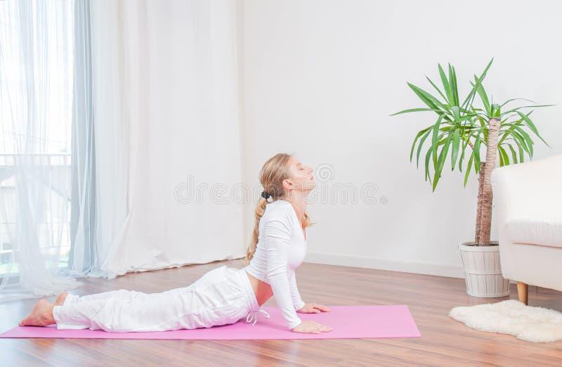 Красивая женщина практикует йогу дома на циновке йоги, делая тренировку кобры, представление Bhujangasana стоковое изображение rf