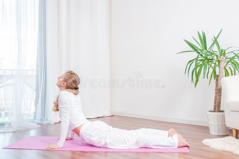 Красивая женщина практикует йогу дома на циновке йоги, делая тренировку кобры, представление Bhujangasana стоковая фотография
