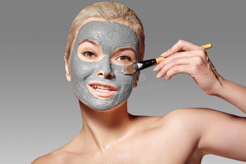 Красивая женщина прикладывая маску глины лицевую Косметические процедуры Девушка спа прикладывает маску глины лицевую с щеткой кр стоковое фото rf