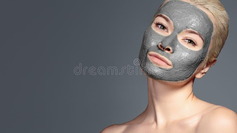 Красивая женщина прикладывая черную лицевую маску Косметики Девушка спа прикладывает маску глины лицевую на серой предпосылке стоковые фотографии rf