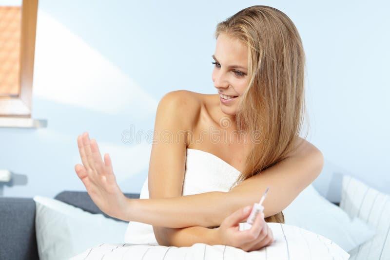 Красивая женщина прикладывая красный маникюр стоковое изображение