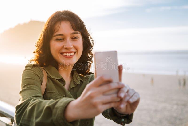 Красивая женщина принимая selfie с ее телефоном на пляже стоковые фото