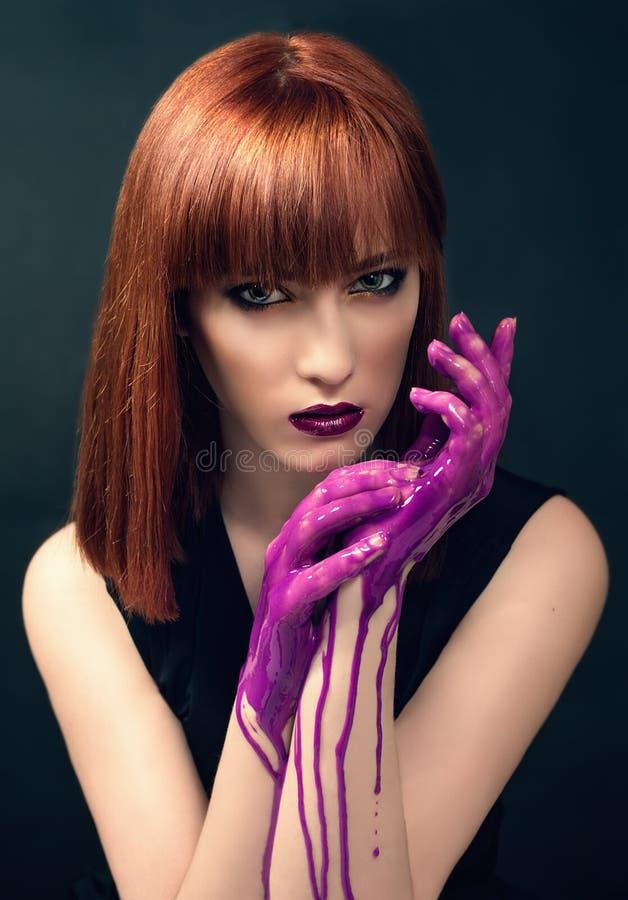 Красивая женщина при пальцы предусматриванные в краске стоковая фотография rf