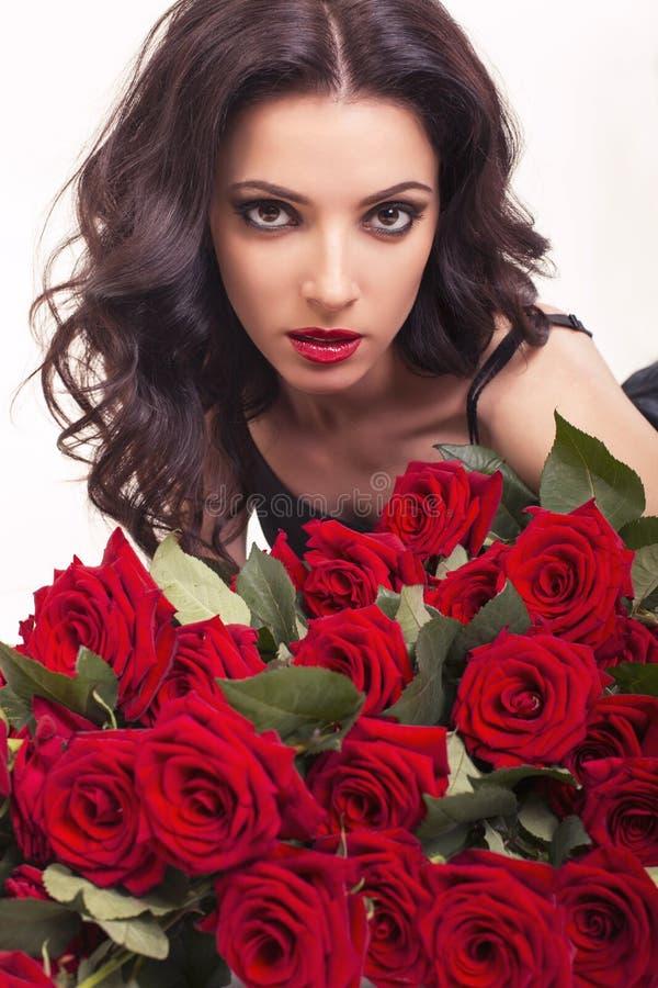 Красивая женщина при темные волосы представляя с большим букетом роз стоковая фотография rf