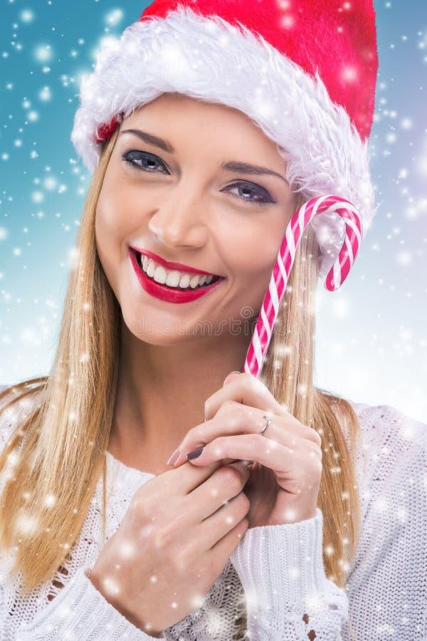Красивая женщина при шляпа santa держа красный ый-бел леденец на палочке рождества стоковое фото