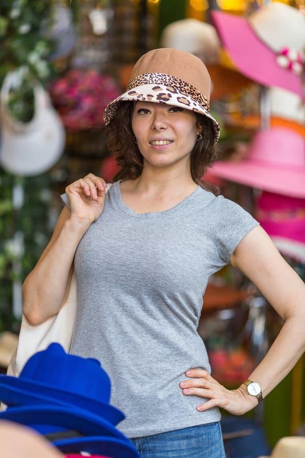 Красивая женщина пробуя на шляпе в магазине стоковое изображение rf