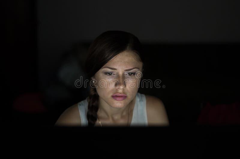 Красивая женщина работая поздно на ноче в офисе стоковые фото