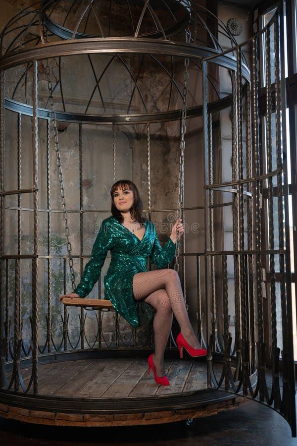 Красивая женщина сидя в клетке самостоятельно из-за ее ограничений и комплексов взрослое женское нося зеленое выравниваясь платье стоковое изображение