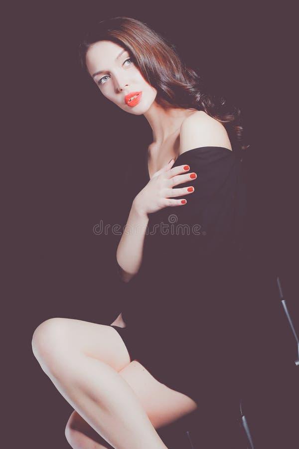 Красивая женщина сидя изолированный стул, на предпосылке недостатка красивейшая женщина стоковая фотография rf