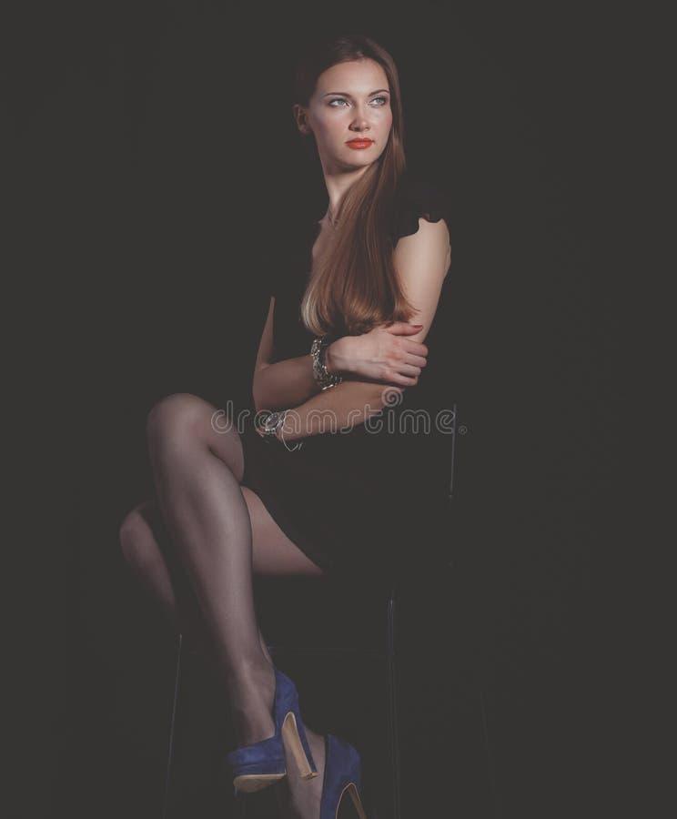 Красивая женщина сидя изолированный стул, на черной предпосылке красивейшая женщина стоковые фотографии rf