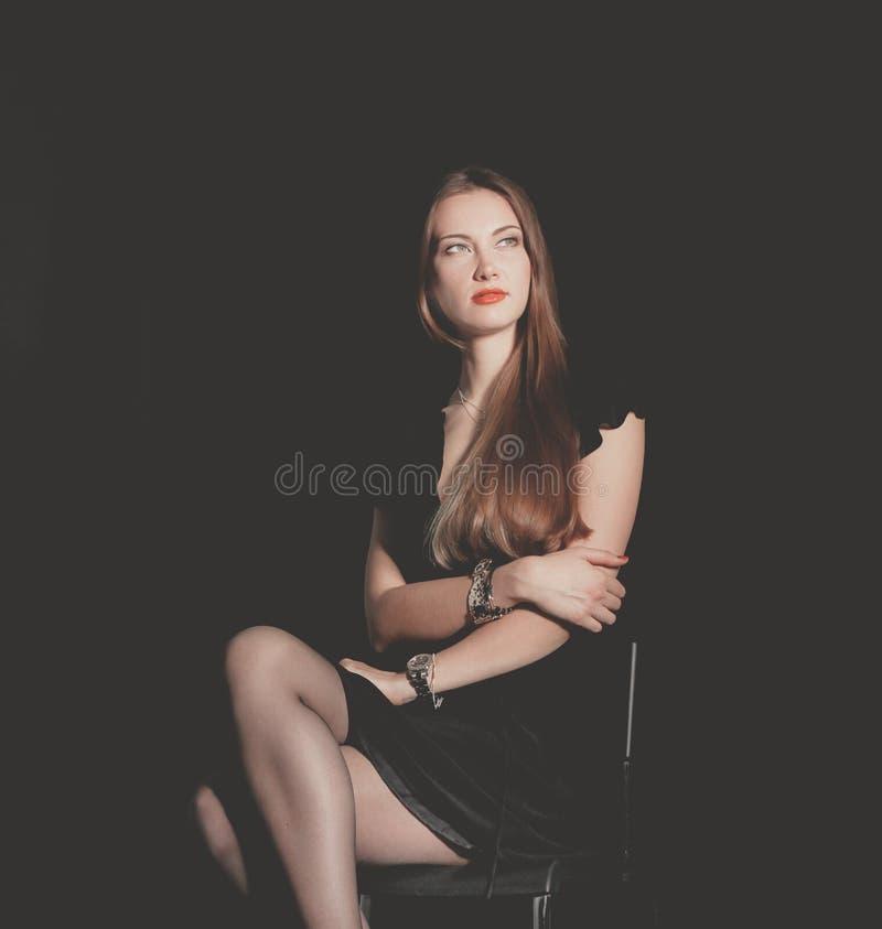 Красивая женщина сидя изолированный стул, на черной предпосылке красивейшая женщина стоковое фото