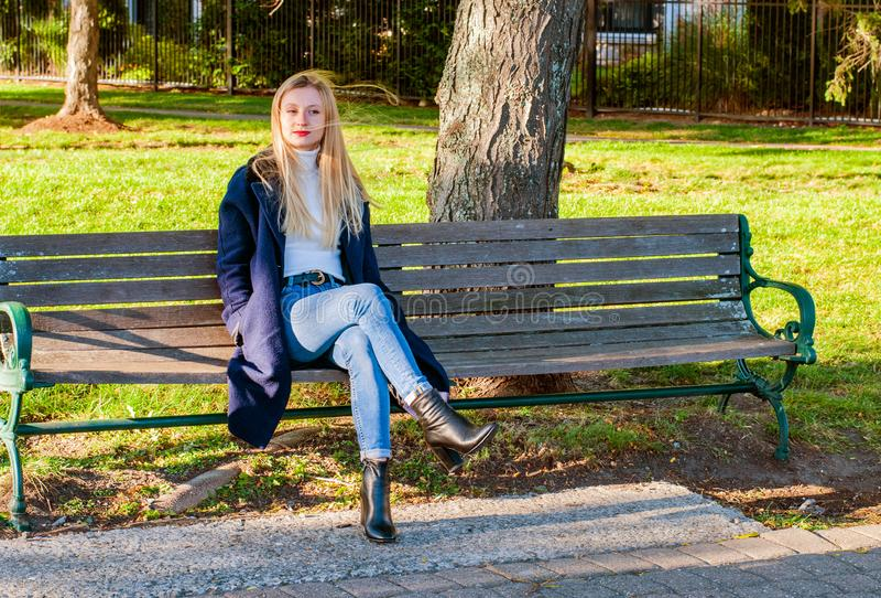 Красивая женщина сидя на стенде в солнечном дне осени в парке стоковая фотография