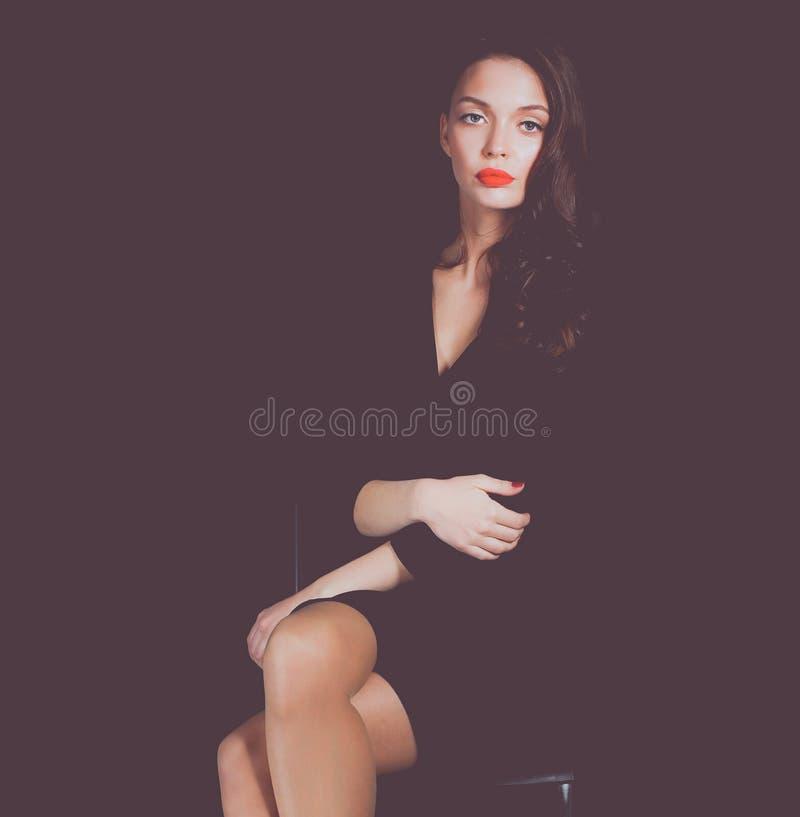 Красивая женщина сидя стул, на предпосылке недостатка красивейшая женщина стоковое изображение