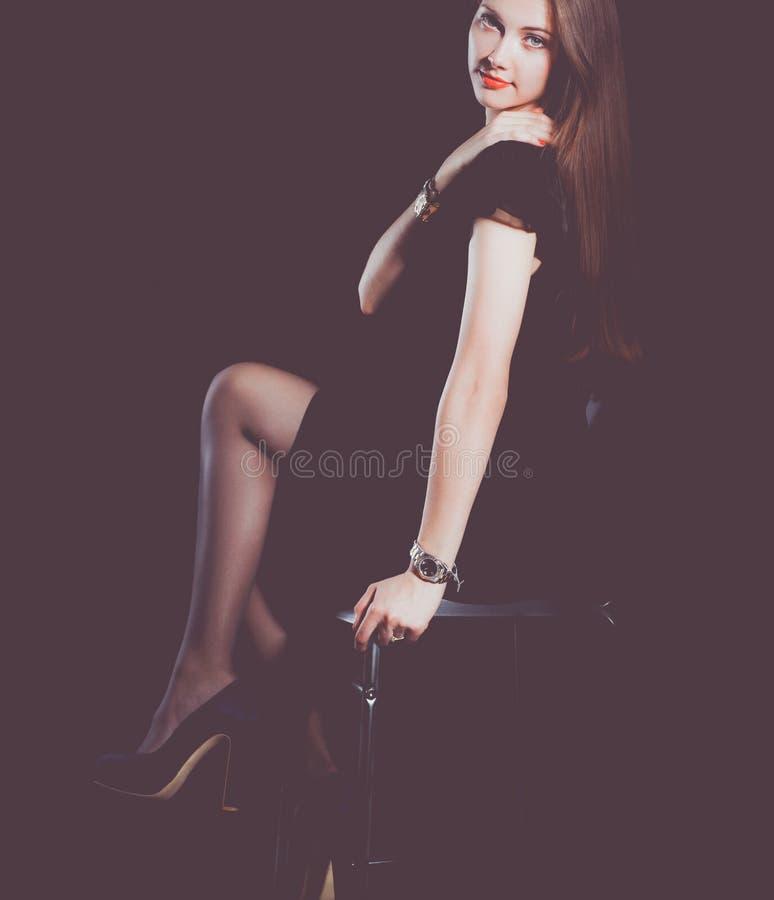 Красивая женщина сидя стул, на черной предпосылке красивейшая женщина стоковая фотография rf