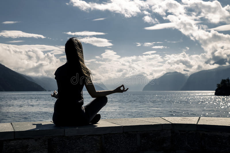 Красивая женщина сидит на береге моря, Норвегии стоковые фото