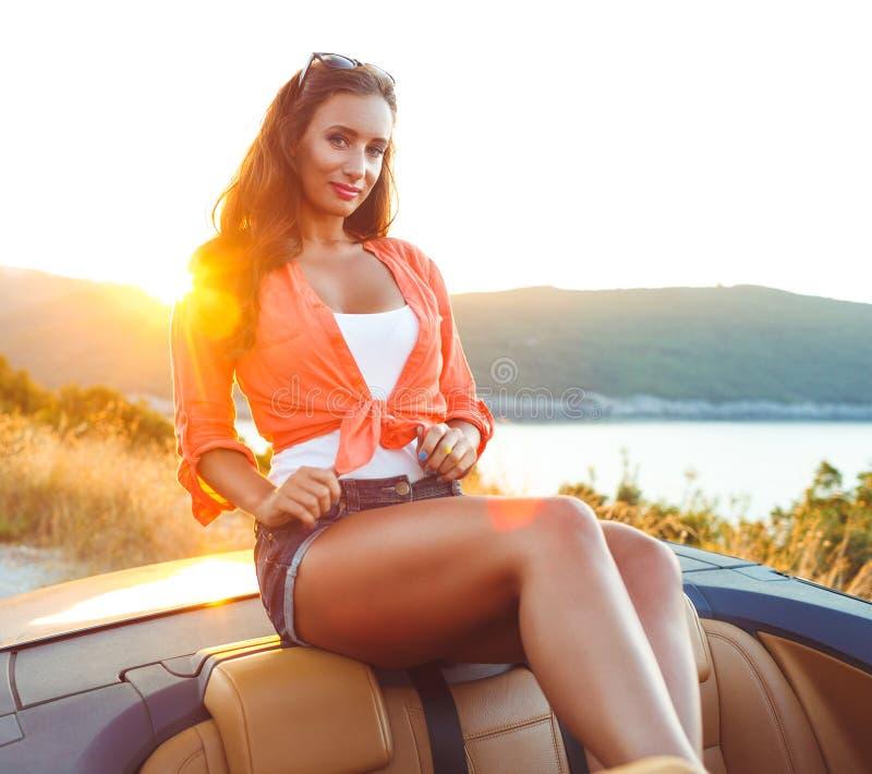 Красивая женщина сидя в cabriolet, наслаждаясь отключением на роскоши mo стоковое фото