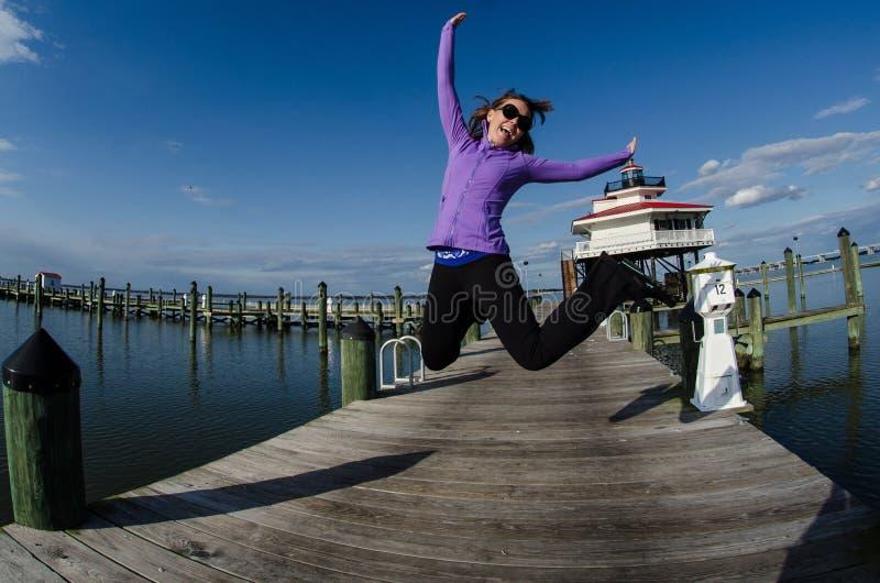 Красивая женщина скачет на док наряду с маяком реки Choptank в Мэриленде стоковые изображения