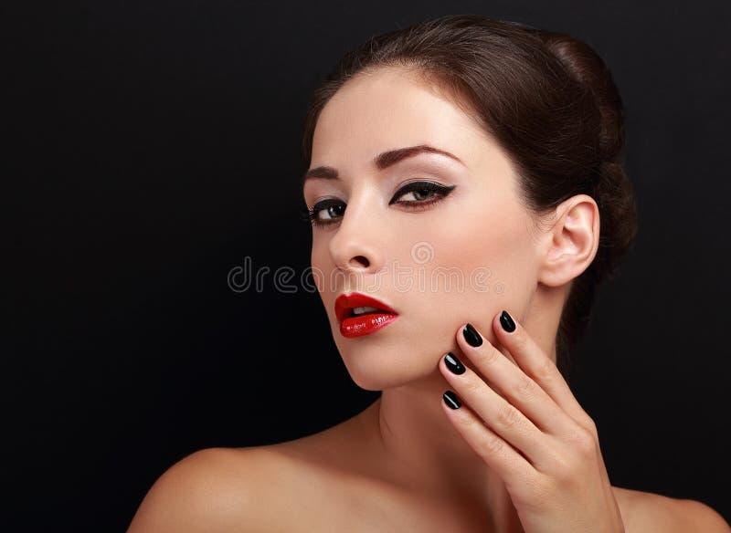 Красивая женщина состава с красными губами и черными ногтями стоковое фото