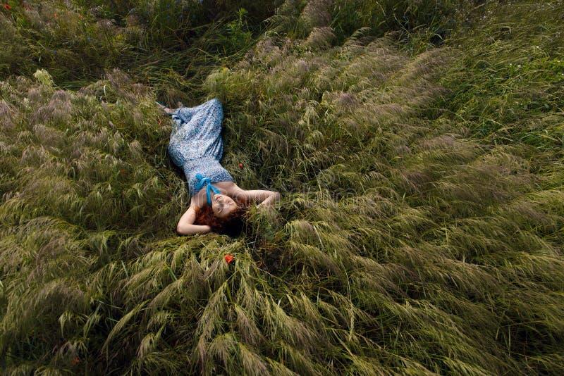 Красивая женщина спать на высокорослой траве стоковое изображение rf