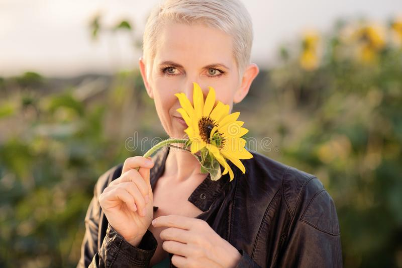 Красивая женщина среднего возраста в сельской сцене поля outdoors стоя между солнцецветами стоковая фотография