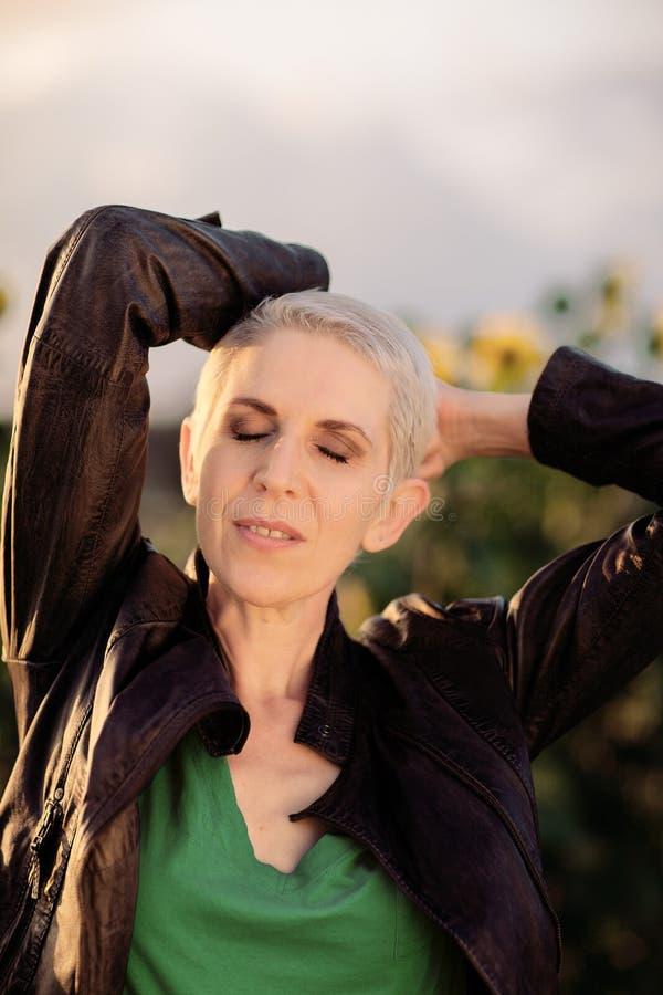 Красивая женщина среднего возраста в сельской сцене поля outdoors стоя между солнцецветами стоковые фото