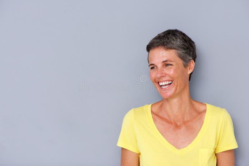 Красивая женщина среднего возраста смеясь над серой стеной стоковые фотографии rf