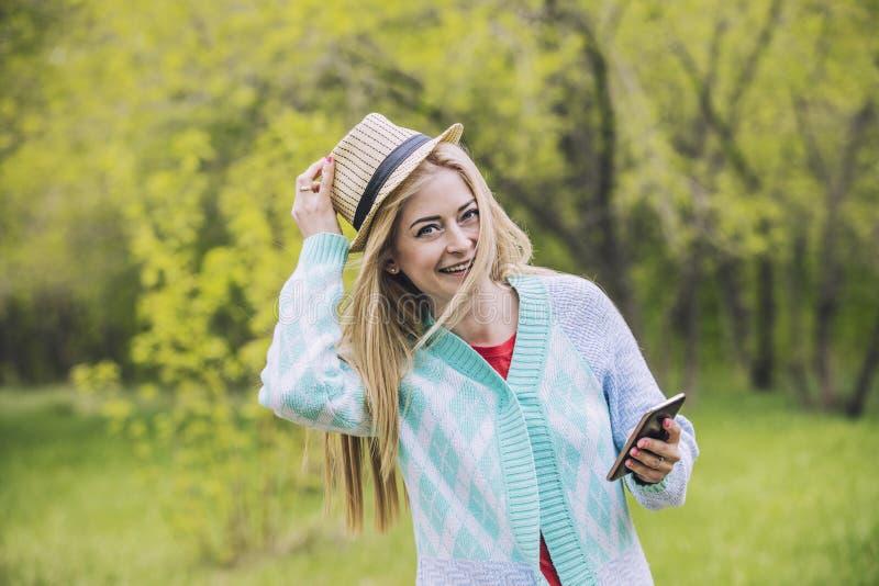 Красивая женщина счастливая и усмехаясь с мобильным телефоном в руке и стоковые фото