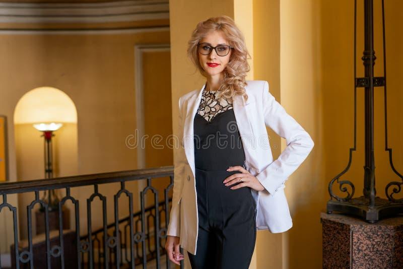 Красивая женщина с белыми волосами в стеклах представляя для камеры стоковое фото