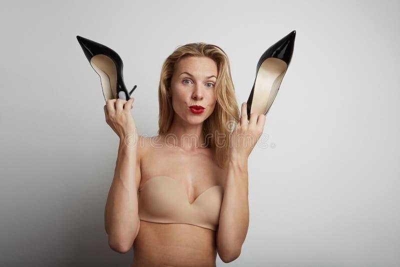 Красивая женщина с ботинками в ее руках стоковая фотография