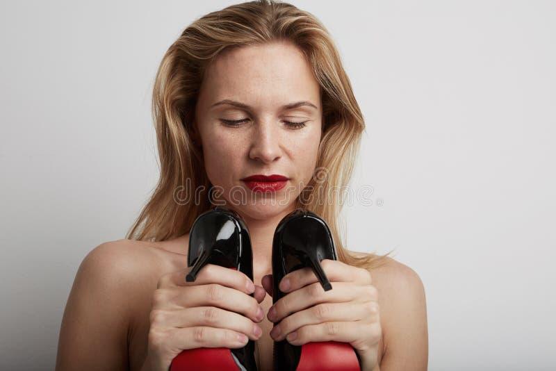Красивая женщина с ботинками в ее руках стоковые изображения rf