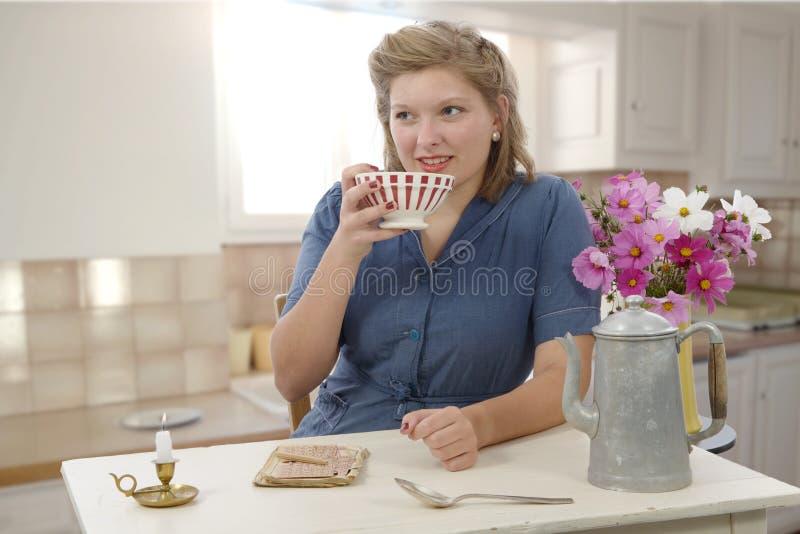 Красивая женщина с винтажными одеждами выпивает кофе стоковое фото rf