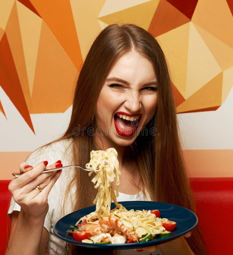 Красивая женщина с выразительно раскрытым ртом есть fettuccine стоковые фотографии rf