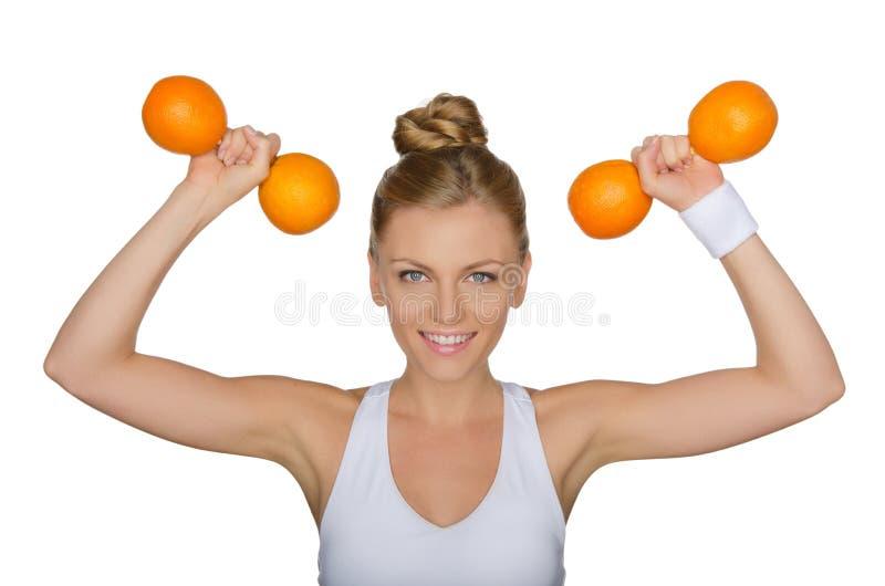 Красивая женщина с гантелями от зрелых апельсинов стоковые фотографии rf