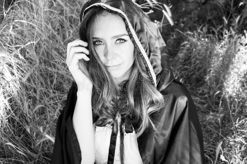 Красивая женщина с голубыми глазами, длинными коричневыми волосами и клобуком в взглядах древесин камера стоковое изображение rf
