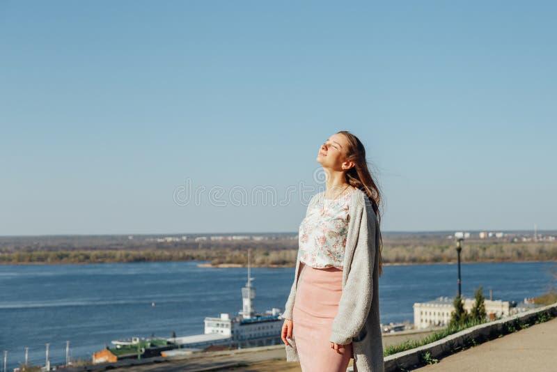Красивая женщина с длинными волосами наслаждаясь видом на город от моста на солнечный день стоковые изображения