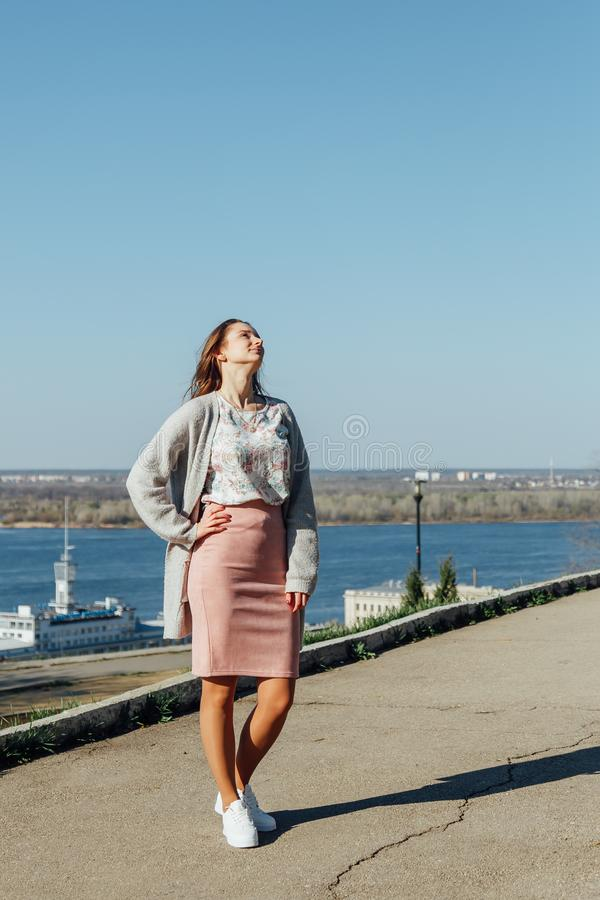 Красивая женщина с длинными волосами наслаждаясь видом на город от моста на солнечный день стоковое фото rf