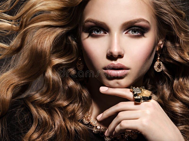 Красивая женщина с длинными ювелирными изделиями вьющиеся волосы и золота стоковая фотография rf