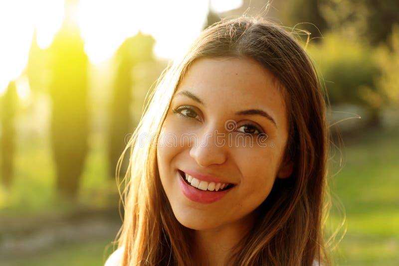 Красивая женщина с забеливает идеальную улыбку на открытом воздухе с зеленой предпосылкой стоковое изображение