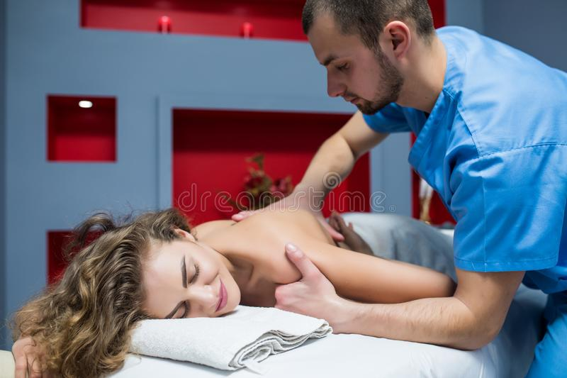 Красивая женщина с закрытыми глазами в салоне курорта получая массаж стоковое изображение
