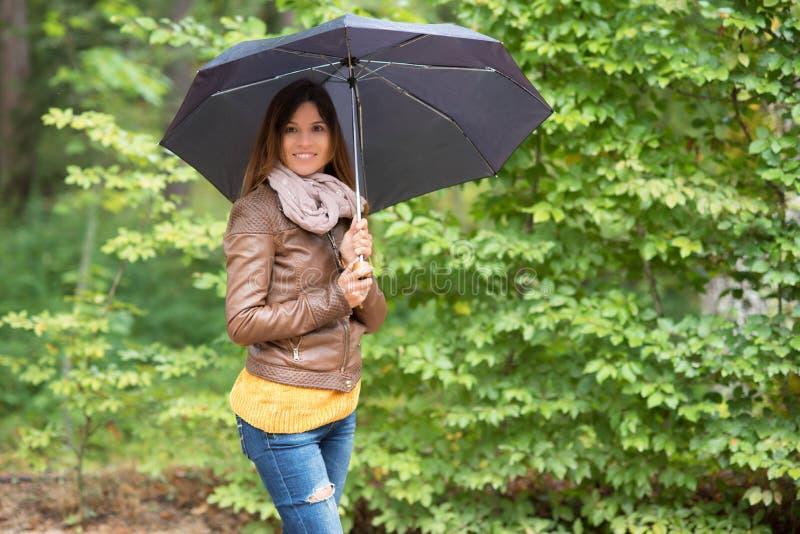 Красивая женщина с зонтиком в парке осени стоковые фото